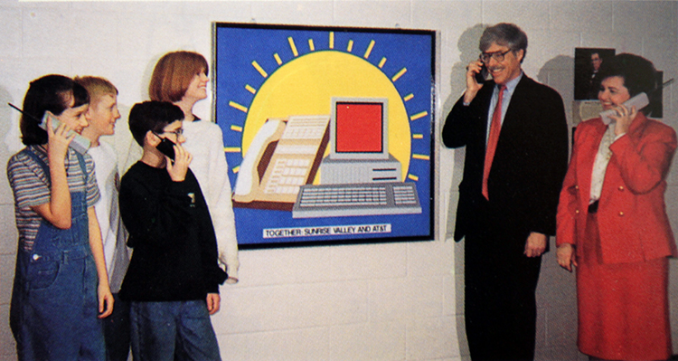 Yearbook photograph of three students, a teacher, Principal Chung, and a representative from AT&T. They are holding wireless telephones in their hands and are standing in front of a painting of a phone and computer. Beneath the computer are the words Together Sunrise Valley and AT&T.
