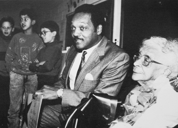 Black and white yearbook picture of Reverend Jesse Jackson seated next to Ms. Ella Miller in a classroom. Three students stand nearby in the background.