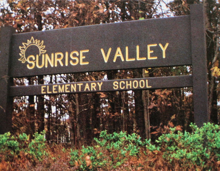 Yearbook photograph of a wooden sign that once stood in front of Sunrise Valley Elementary School. It is a dark brown sign with gold letters that read Sunrise Valley Elementary School.