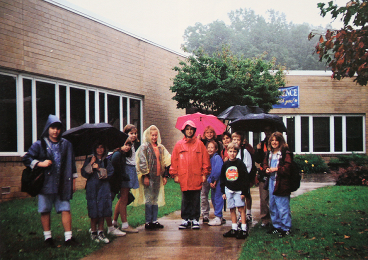 Yearbook photograph of a group of students standing on the sidewalk in front of Sunrise Valley Elementary School.