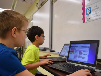 a photo of two students learning with laptops