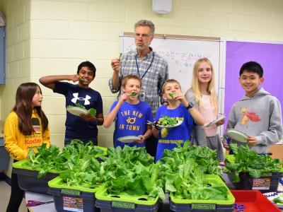 a photo of students and a teacher with lettuce